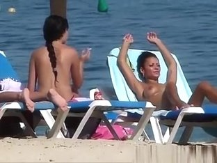 Pretty topless girls sunbathing on the beach