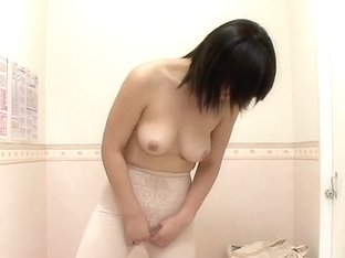 An Asian girl changes her outfit and gets naked in voyeur changing room