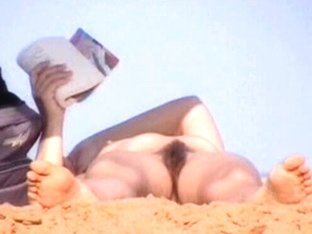 Mature woman lying naked on the beach got her pussy voyeured