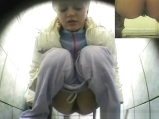 Cute blonde pissing in public toilet