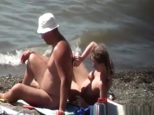 Busty nudist woman sprays her man's back