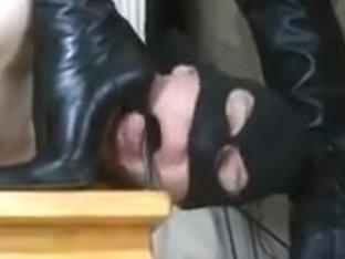 Slave licks latex boots of mistress, who smokes cigar