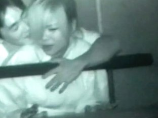 Asian couple making out on stair in public at night