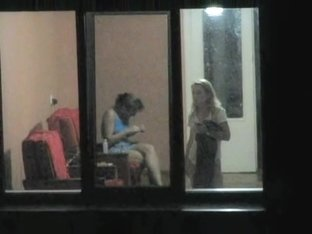 Brunette and blonde girls voyeured through hostel window