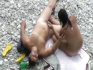 Black hair nudist and her man at beach