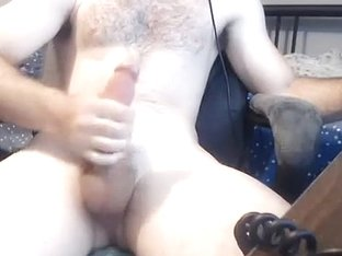 Charming man is relaxing in the apartment and shooting himself on computer webcam
