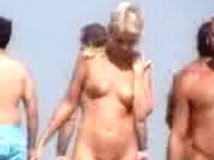Nudist couple filmed while walking on the beach