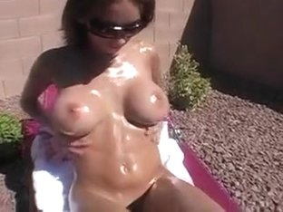 Sunbathing brunette beauty Mandy greases up her marvelous big hooters