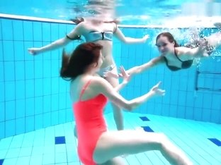 Three nude girls have fun underwater