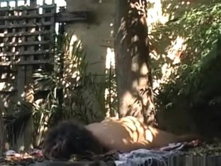 Brunette girl with small tits fingers her shaved pussy on a sheet in nature and moans