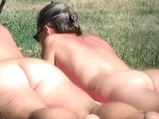 Undressed pair sunbathing in forest meadow