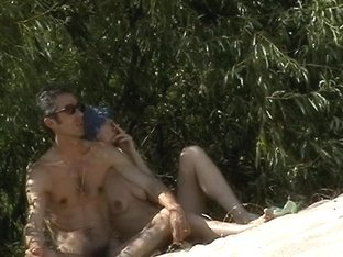 Naked couple taking sunbaths and rest on the beach