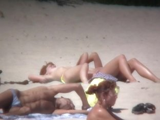Lazy chicks lie on the beach and demonstrate their bodies