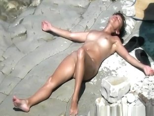 Naturist lady sunbathing by the water