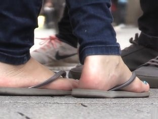 Candid barefoot shoeplay in flip-flops