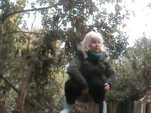 Mature blonde woman pissing
