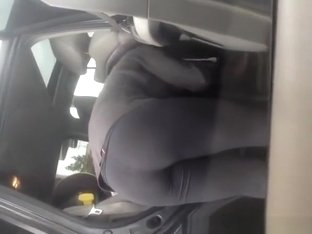 Cleaning the car wearing tight black pants