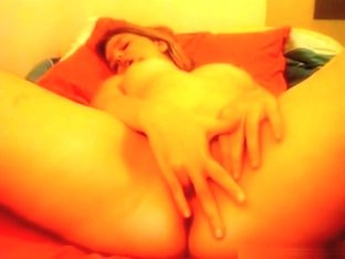 Blonde girl fingers her shaved pussy on her bed and moans