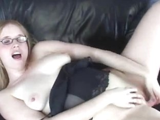Horny nerd chick plays her pussy while laying on the sofa