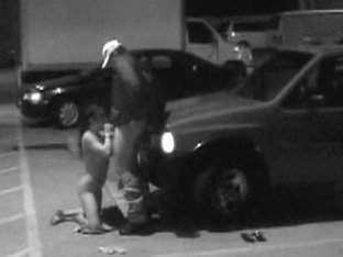 Babe is on knees sucking cock in the parking place in voyeur xxx
