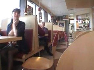 Brunette MILF flashing her jugs in a restaurant