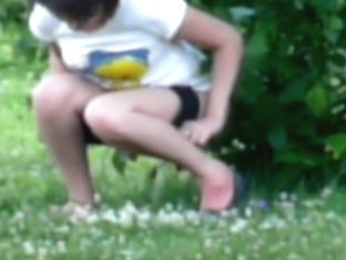Young brunette with sexy legs pissing in the bushes