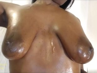Rubbing oil all over my breasts.