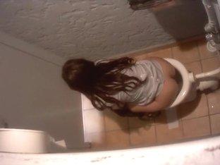 Charming brunette coed gets filmed while taking a whiz