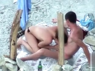 Topless girlfriend sucking his big cock at the beach