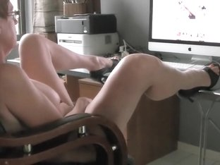 Bespectacled housewife flicks the bean while watching porn