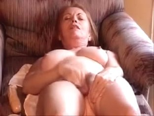 My mature busty wife dildos her unshaved vagina in a living room