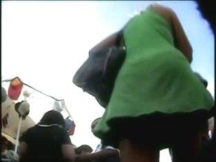 Blondie in a short green skirt has an upskirt voyeur after her