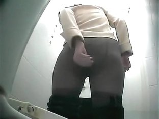 Girl in black jeans pants pissing in toilet