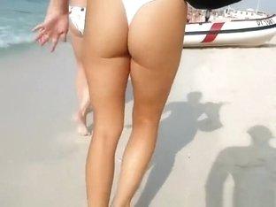 Woman in white bikini thong walking