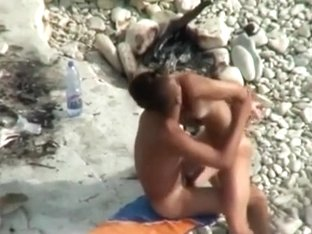 Voyeur tapes a girl playing with her bf's cock on a nudist beach