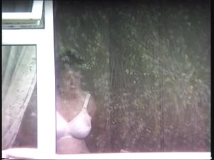 mature neighbor putting on bra