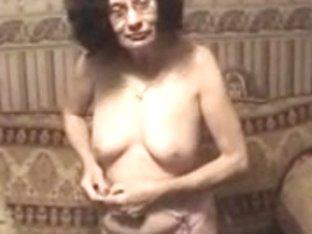 Mature slut strips and masturbates on the sofa